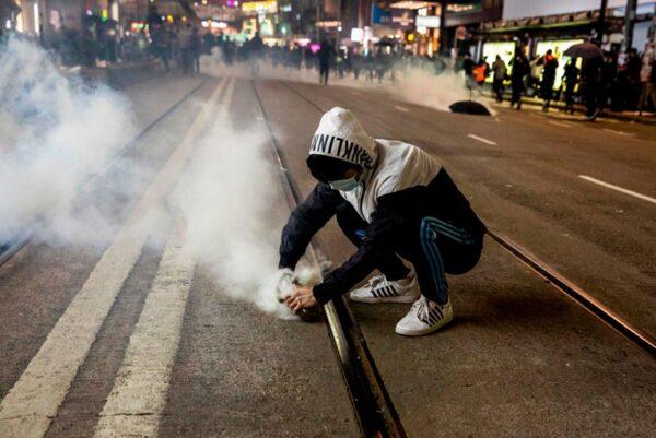 2020年1月1日,103萬港人在新年第一天走上街頭,一名年輕人在熄滅港警發射的催淚彈。(ISAAC LAWRENCE/AFP via Getty Images)