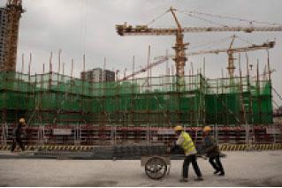 新年伊始,經濟學家關注大陸經濟前景,預計支撐大陸經濟的「三駕馬車」將全部失靈。圖為北京一處建設工地的工人。(AFP)