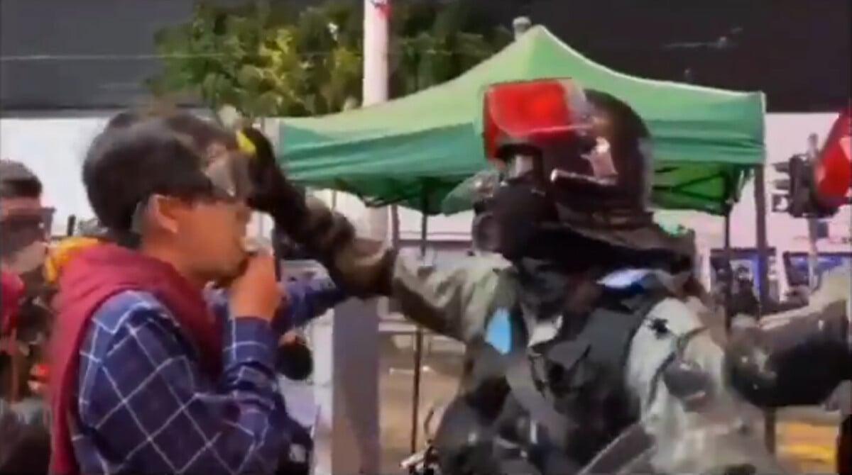 香港立法會民主派議員許智峰正在街頭嘗試向警方人員講理辯論時遭到一名蒙面警員襲擊。(影片截圖)