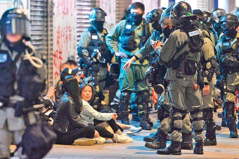1月1日遊行被港警逮捕的抗爭者集中在一起,最後送上大巴離開。(大紀元)