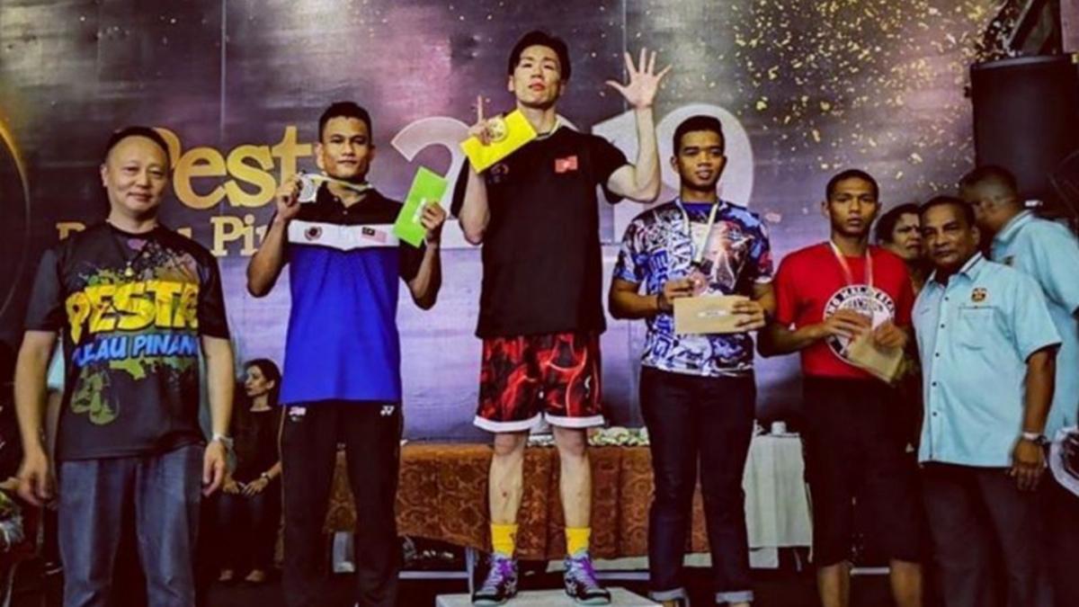 香港拳擊選手袁文俊於國際賽事勇奪金牌,在頒獎舞台上,他高舉「五大訴求、缺一不可」手勢。(圖取自IG @dayemerson)
