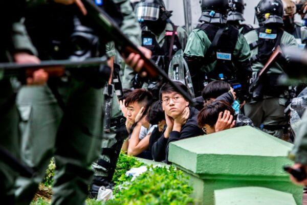 1月5日,港警無差別拘捕上百名遊行抗議的市民。港警逼迫民眾跪地及雙手放頭,如同對待戰俘。(ISAAC LAWRENCE/AFP via Getty Images)