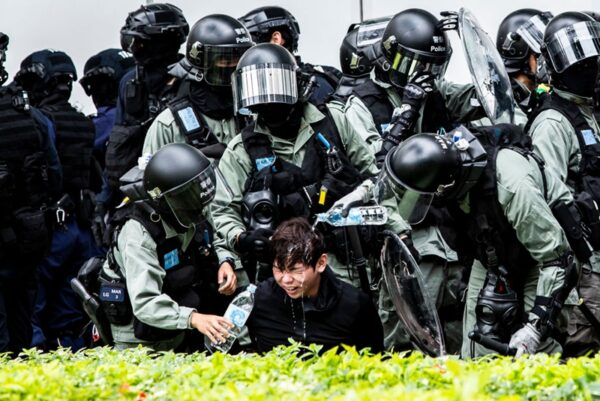 一名便衣警察被放暴警用胡椒噴霧噴面,表情痛苦,港警幫其洗臉。(ISAAC LAWRENCE/AFP via Getty Images)
