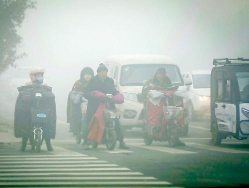 大陸多地遭新年首輪「霾伏」,69 個市啟動重污染預警。圖為去年 12 月 7日,人們在陰霾籠罩的山東菏澤曹縣街頭騎行。( 大紀元資料室)