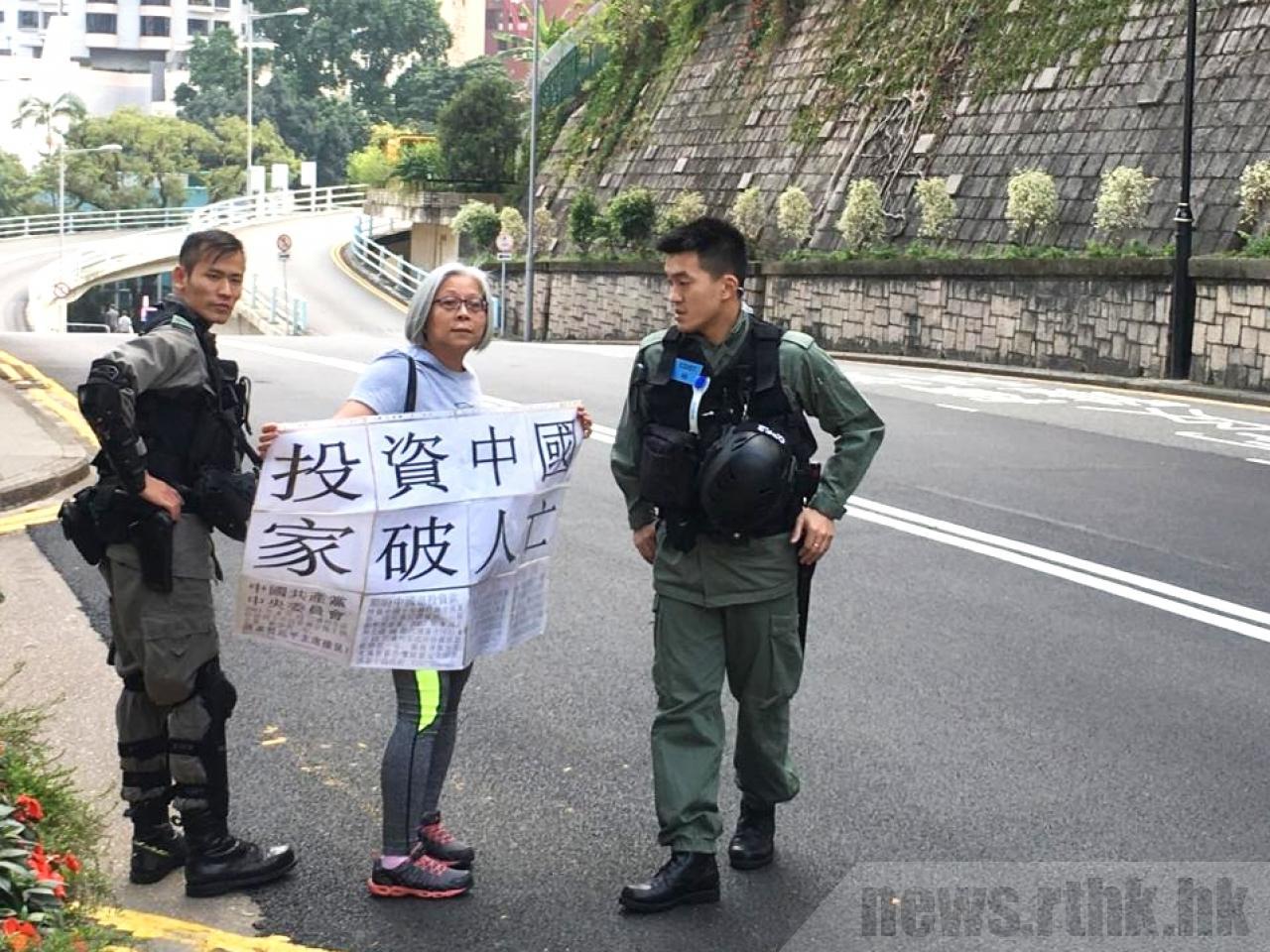 有市民手持標語到禮賓府示威,被防暴警員驅趕離開。(圖片來源:香港電台)