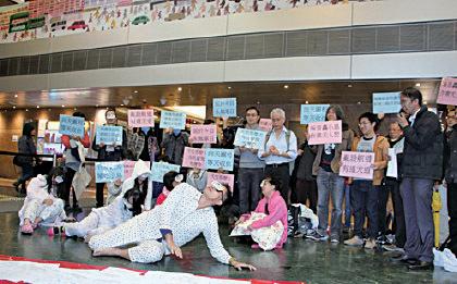 數十名馬灣居民,穿睡衣睡袍、戴佈滿血絲的眼睛演短劇,表達長期飽受飛機聲噪音難以入睡的痛苦。(蔡雯文/大紀元)