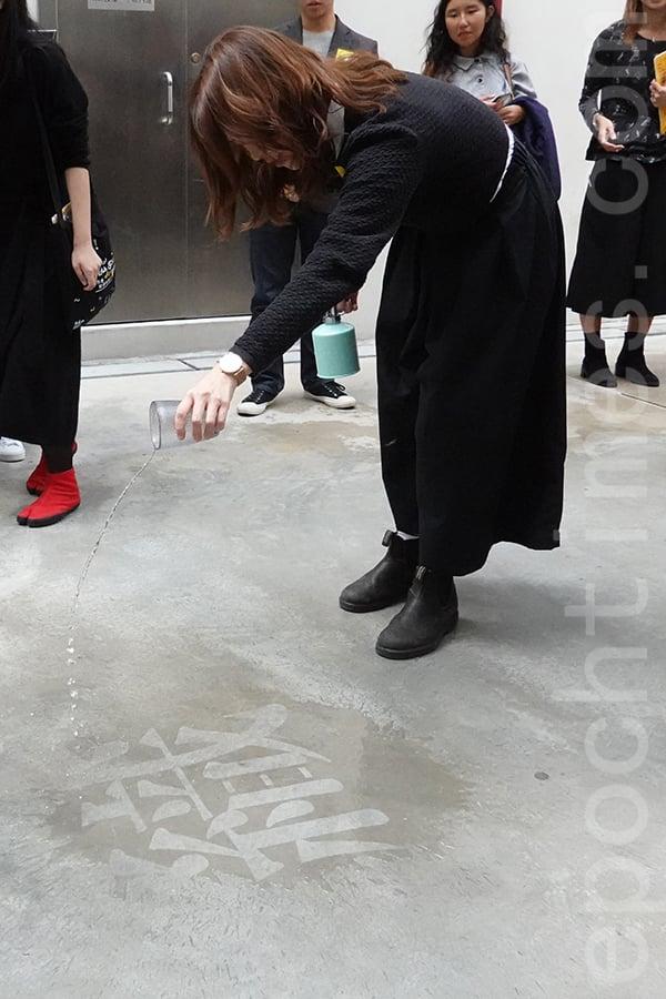 林丰、陳韻淇創作的藝術裝置《字間遊》,體現《香草織》中的場景,若隱若現的字體需要浸濕方能明顯顯示。(曾蓮/大紀元)