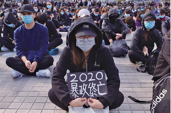 一名抗爭者手持「暴政終亡」紙牌,控訴中共及港府暴政。(余鋼/大紀元)