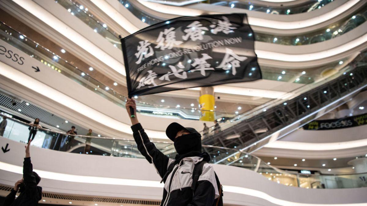 中國香港一名示威者於2020年1月11日在銅鑼灣時代廣場商場內揮舞反政府示威旗幟。(Laurel Chor/Getty Images)