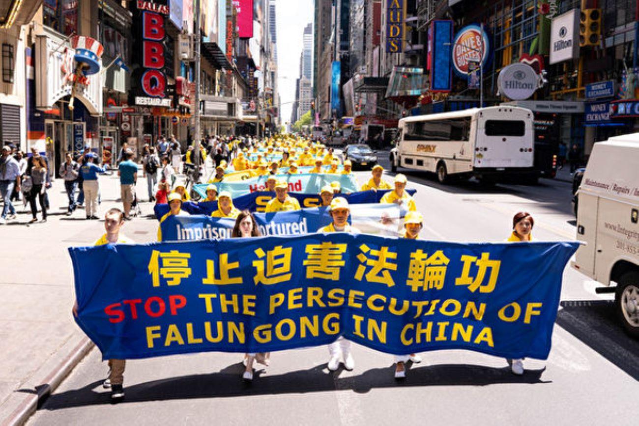 圖為2019年5月16日,紐約,法輪功學員在大遊行中以橫幅呼籲中共停止迫害。(戴兵/大紀元)