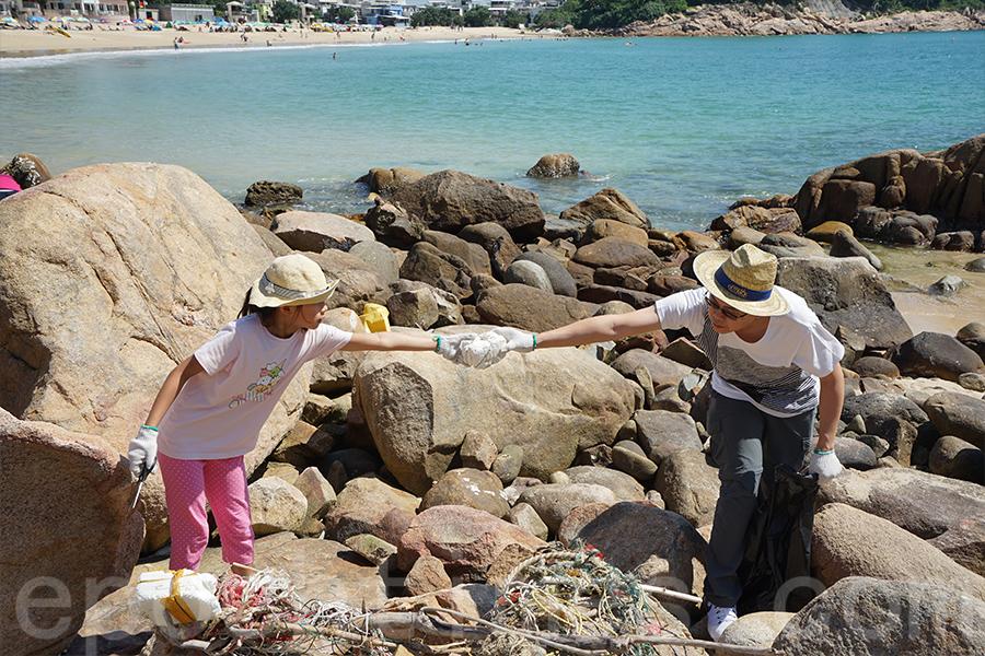 家長與孩子們身體力行,在清潔海灘過程中體會「走塑」的重要性。(陳仲明/大紀元)