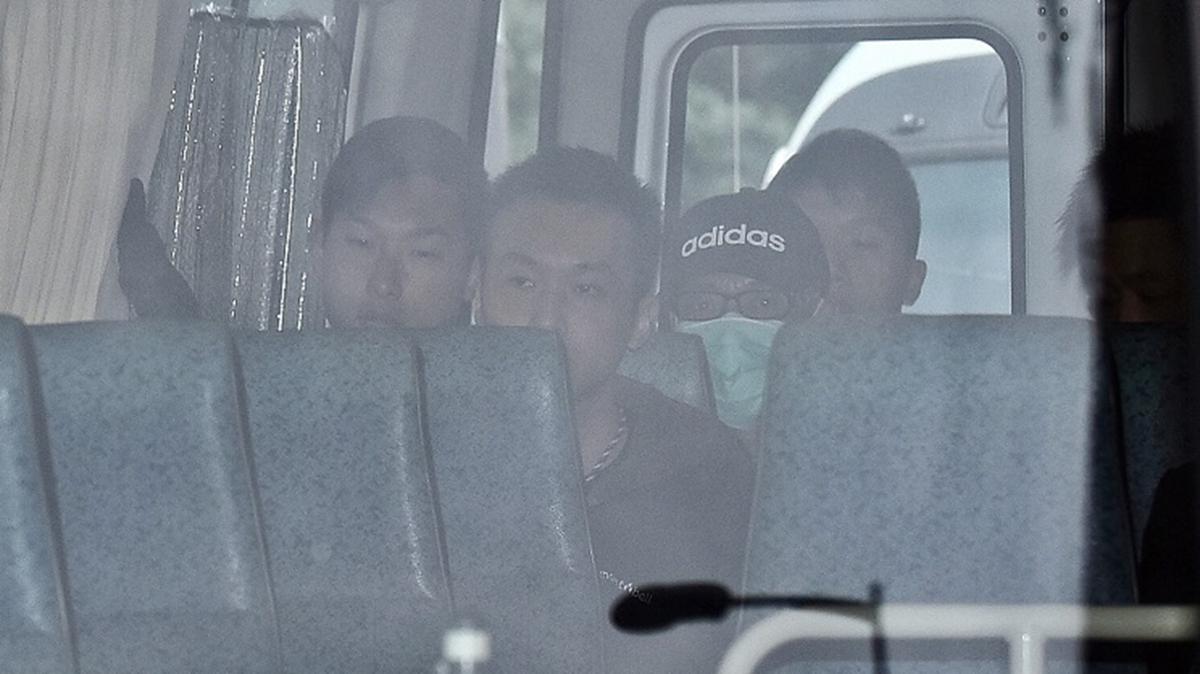 季炳雄(戴黑帽口罩者)2020年1月18日早上出獄,他在多輛警車押解下,直赴機場遞解到美國。(中央社)