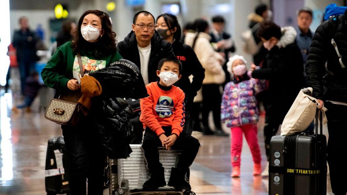 圖為北京機場,一些旅客戴口罩以防護中共病毒。(NOEL CELIS/AFP via Getty Images)