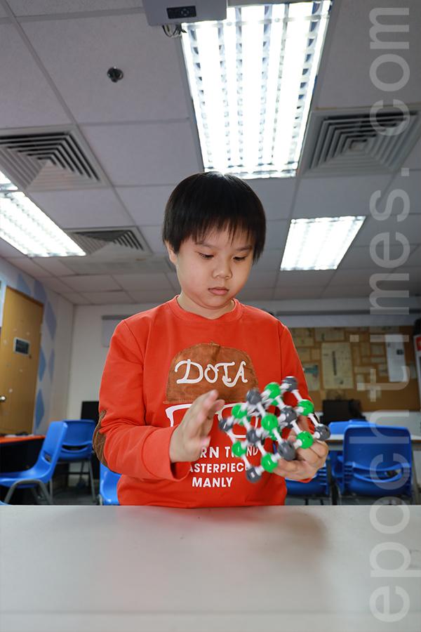 柯熙町已經開始學習高中的化學方程式和各類分子結構,鹽的分子結構圖不足兩分鐘就堆砌出來。(陳仲明/大紀元)