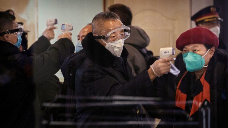 北京已淪陷,火車站工作人員對旅客測體溫,排查中共肺炎疫情。 (Kevin Frayer/Getty Images)