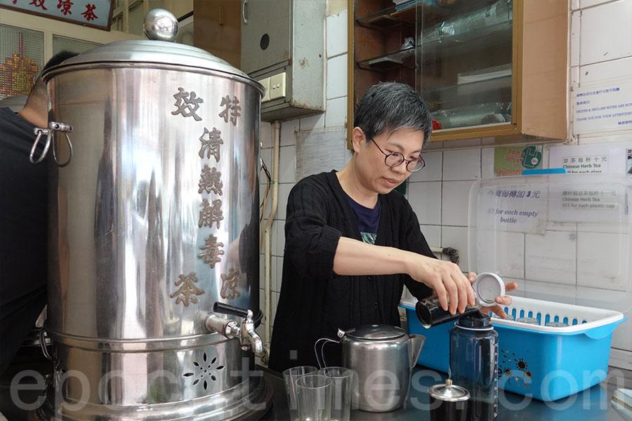 有顧客用自己帶的水樽盛載五杯涼茶,楊翊鈴將涼茶注入水樽中。(曾蓮/大紀元)
