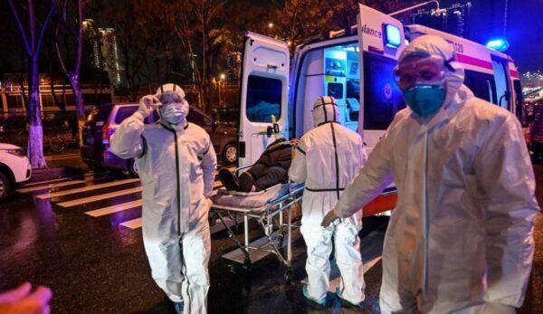 25日武漢醫務人員正運送病人。(HECTOR RETAMAL/AFP VIA GETTY IMAGES)
