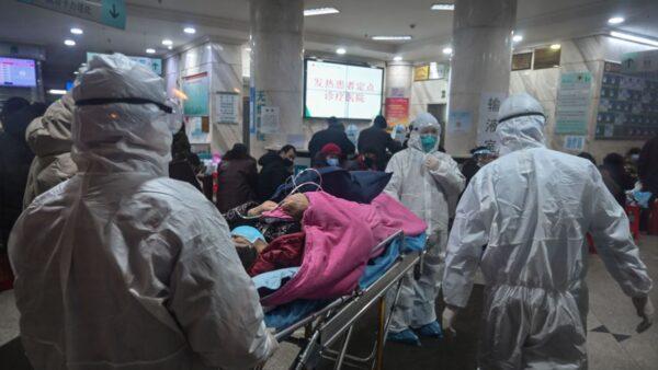 武漢肺炎疫情大爆發,圖為醫護人員收治病人。(HECTOR RETAMAL/AFP via Getty Images)