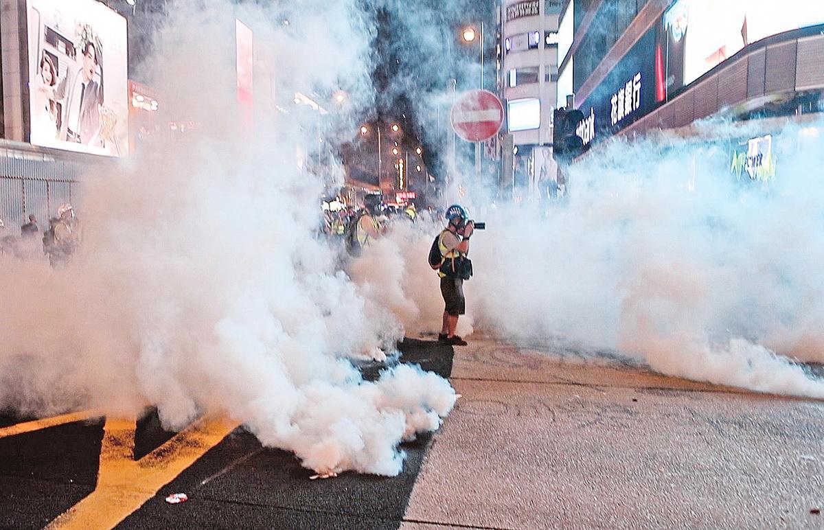 2019年10月27日,市民發起「追究警暴,守護民眾,與記者同行」尖沙咀集會。圖為被催淚煙包圍的記者。(余鋼/大紀元)