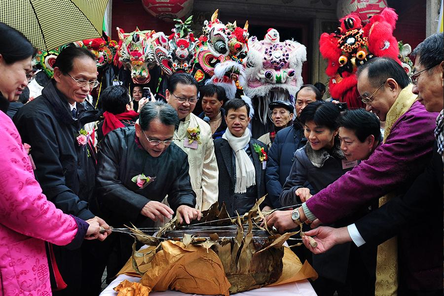 一年一度的坑口麒麟醒獅新春團拜活動中,眾人分享圓籠茶粿。(張浩林提供)