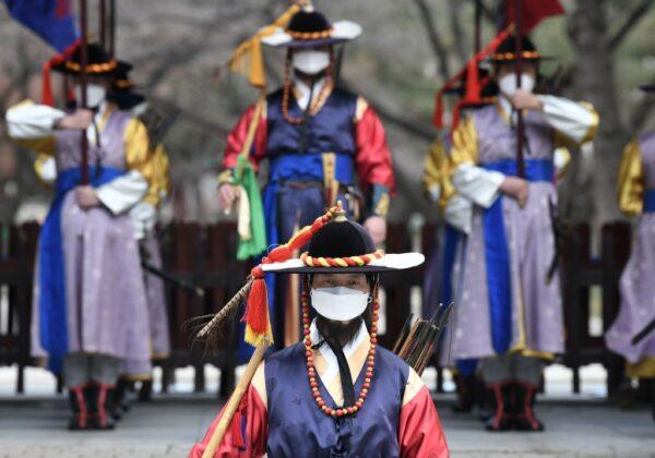 2020年1月30日,身穿南韓傳統服裝的「宮殿護衛」成員在首爾的德壽宮為遊客表演時戴上口罩。(JUNG YEON-JE/AFP via Getty Images)