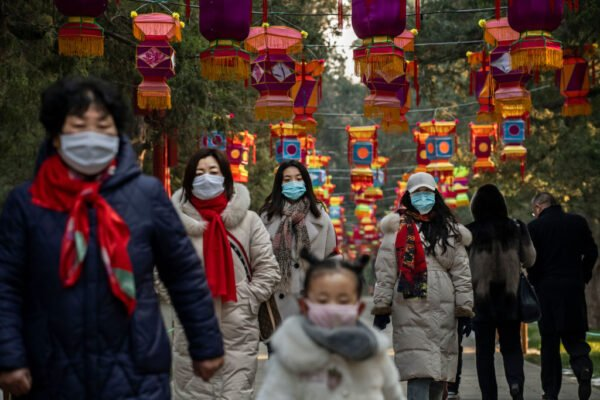 2020年1月25日,中國北京取消慶祝活動。圖為民眾戴口罩走在公園的裝飾下。(Kevin Frayer/Getty Images)