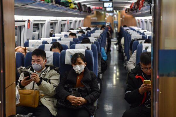 2020年1月23日,上海虹橋火車站,乘客戴著口罩坐火車。(HECTOR RETAMAL/AFP via Getty Images)