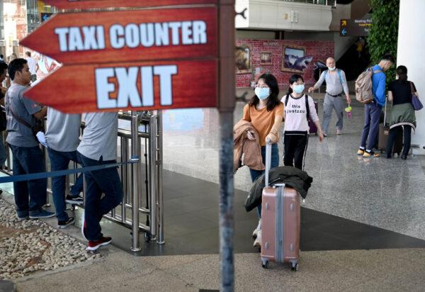圖為,2020年1月23日,戴著口罩的中國遊客抵達印尼度假勝地峇里島的伍拉·賴國際機場。(SONNY TUMBELAKA/AFP via Getty Images)