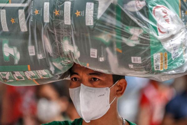 2020年1月31日,菲律賓民眾對中共病毒的恐懼加劇,大批人群聚集醫療用品商店搶購口罩。圖為一名男子頭頂買到的一袋口罩。(Ezra Acayan/Getty Images)