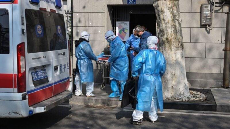 圖為1月30日武漢醫護人員帶走一名感染中共肺炎的病人。(HECTOR RETAMAL/AFP via Getty Images)