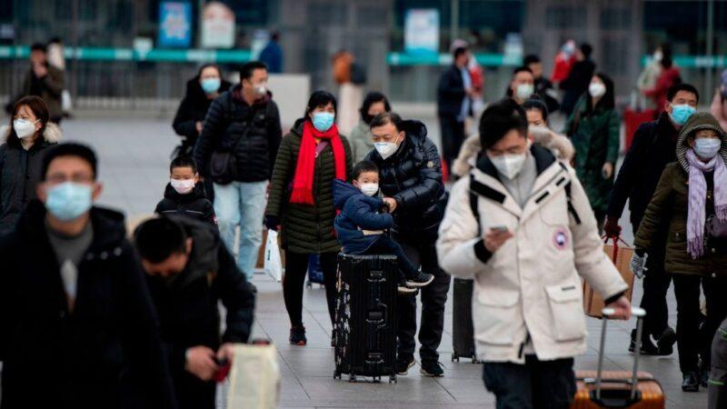 2020年2月1日,乘客戴著口罩,從不同省份到達北京火車站。(NOEL CELIS/AFP via Getty Images)