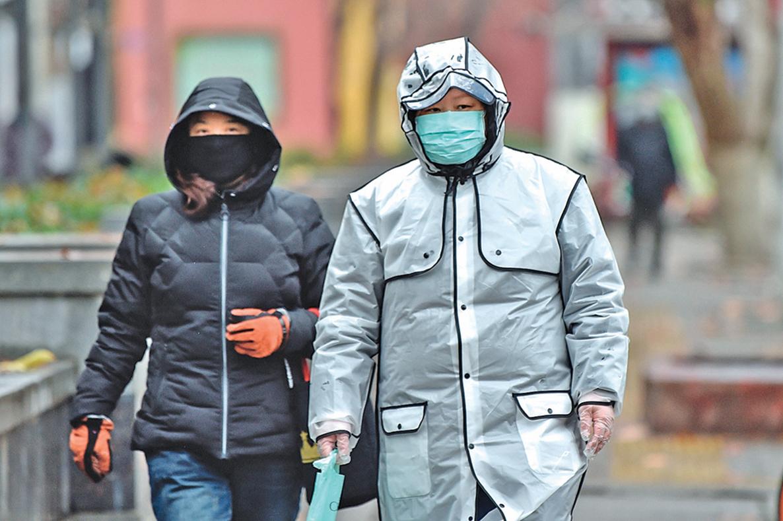 武漢封城已一週,當地民眾反映,封城後生活艱難,心裏感到很絕望。圖為武漢一家醫院前兩名戴著防護口罩的市民。(AFP)