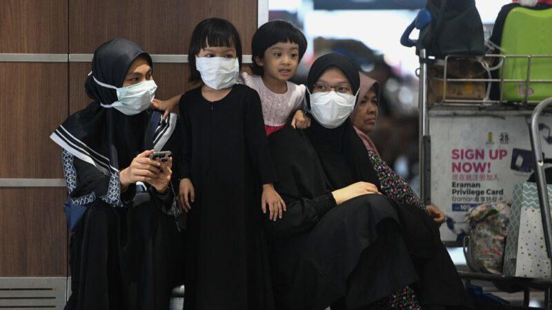 2020年2月4日,乘客抵達吉隆坡國際機場時,戴上防護口罩。(MOHD RASFAN/AFP via Getty Images)