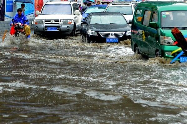 2016年7月18日,悶熱天氣之後,一場突如其來的降雨讓蘭州一下子進入了「看海」模式,路面的積水為市民出行帶來了不少困擾,部分地區由於水位較高,市民只能紛紛脫鞋,「踩水」通行。(大紀元資料室)