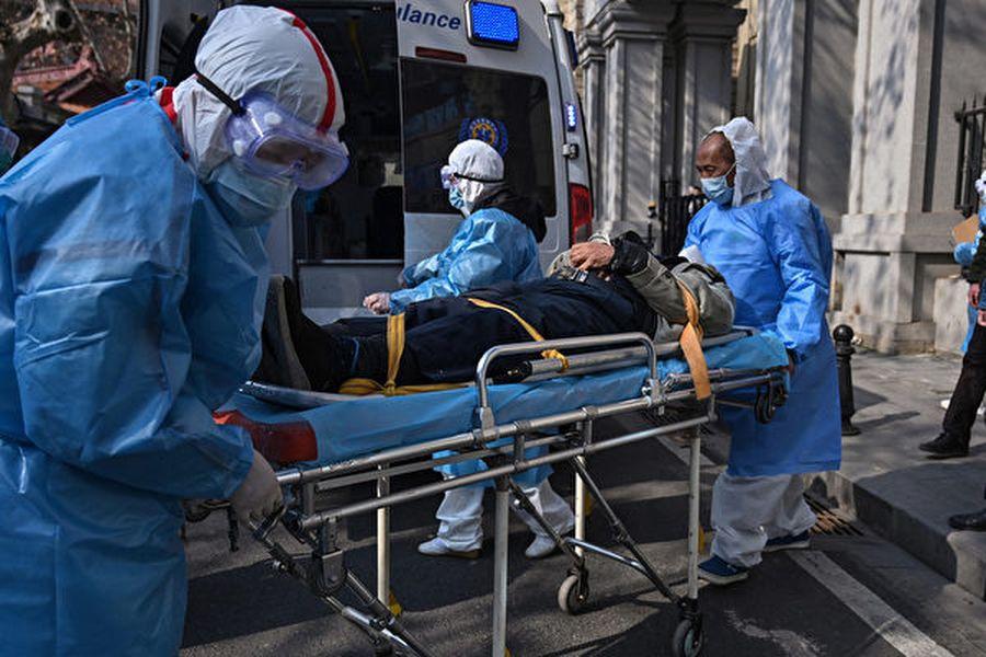 最近,湖北及武漢紅十字會因分配捐贈物資不公、造假陷入輿論漩渦。圖為武漢醫務人員帶走一名疑似感染的患者。(Hector RETAMAL/AFP)