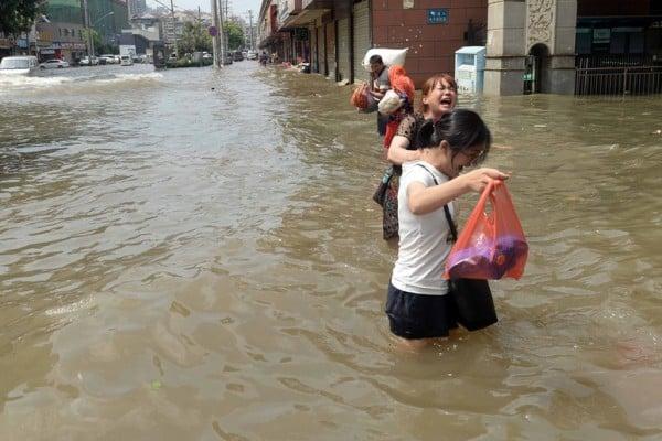 2016年7月7日,湖北武漢,暴雨過後,道路遭洪水淹没,民眾涉水行走。(STR/AFP/Getty Images)