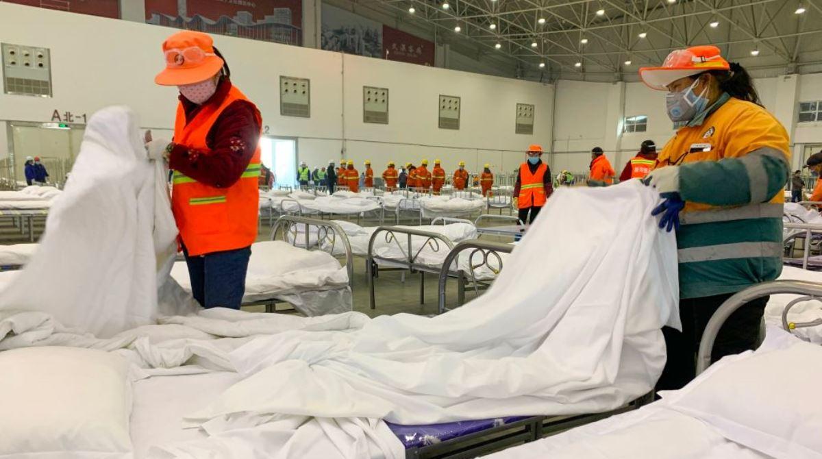 圖為中國正爆發中共肺炎疫情的武漢市一些工人們2020年2月4日在一個由展覽中心臨時改建的隔離區擺放病床。(ySTR/AFP via Getty Images)