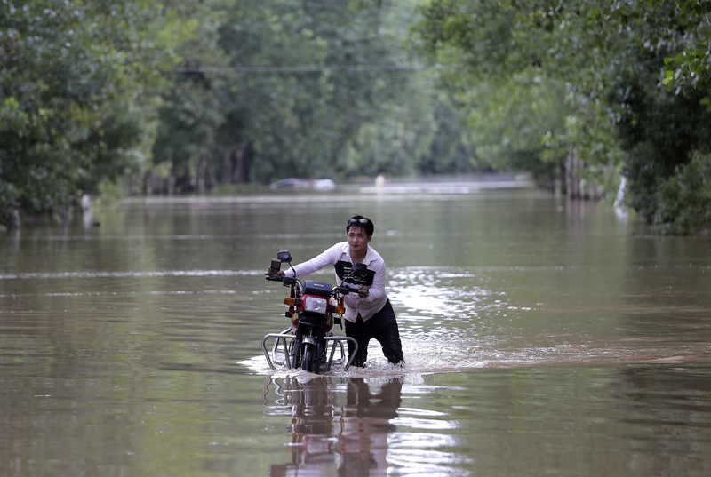 2016年7月3日,湖北武漢,河水缺堤,一名村民在洪水中走路。(Wang He/Getty Images)