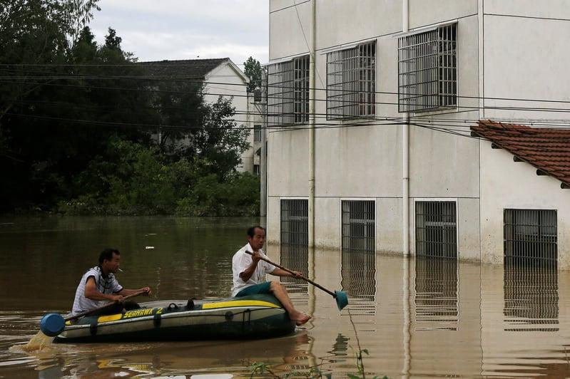 2016年7月3日,湖北武漢,洪水淹没民宅,民眾以小艇代步。(Wang He/Getty Images)