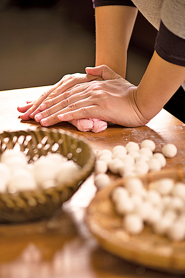 「搓湯圓」。先用軟滑的糰子為基底,把糯米粉屑黏合成糰,再分成小塊,搓成圓。(龔安妮/大紀元)