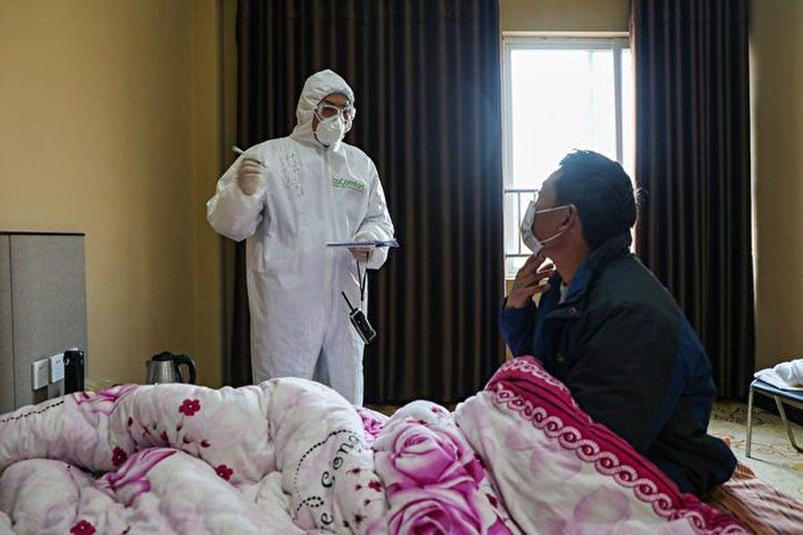 反共富豪郭文貴在2月3日爆料說,中國因中共肺炎而死亡的人數已有3萬人以上。圖為2020年2月3日,武漢一所醫院內的醫生與病人談話。(STR/AFP via Getty Images)
