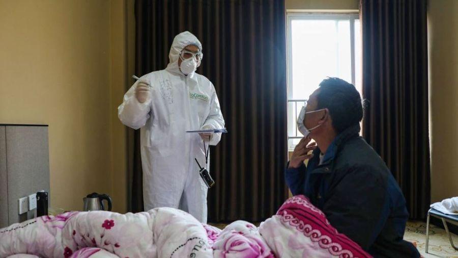 這張攝於2020年2月3日的照片顯示,中國已爆發了中共病毒疫情的湖北省武漢市某醫院的一名醫生(左)在隔離區的病房裏巡視病人病情。(STR/AFP via Getty Images)