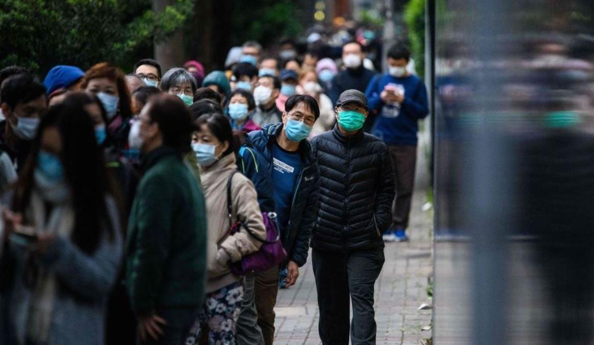 由於中國武漢市中共病毒疫情持續蔓延,香港民眾2020年2月5日戴著口罩排隊等候從臨時攤位獲得預售票去購買口罩。(ANTHONY WALLACE/AFP via Getty Images)