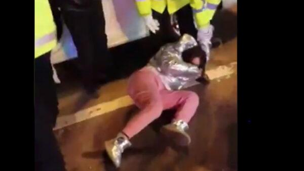 影片顯示,一女子開車上路,被警察攔截按倒在地,昏死了過去。(影片截圖)