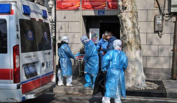 圖為武漢市醫務人員從一間公寓中帶走一名患者。(HECTOR RETAMAL/AFP via Getty Images)