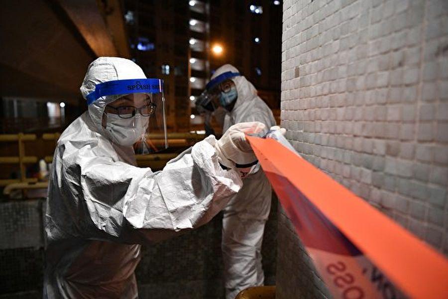 周二(2月11日),香港中共肺炎確診病例達到49例,美國國務院授權非緊急駐港官員及眷屬撤離,另外,香港同棟大樓出現兩宗病例,港府正在調查中共病毒是否會從管道傳播。圖為2020年2月11日凌晨,穿著防護服的警務人員於在香港青衣新界長康村康美樓住宅區的地面上設置了警戒線,此前該街區的兩個人被證實感染了中共病毒。(Photo by Anthony WALLACE/AFP)