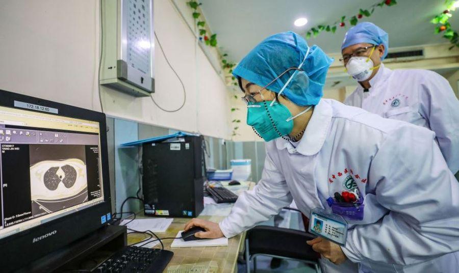 這張攝於2020年1月30日的照片顯示,在中國湖北省武漢市爆發中共病毒疫情期間,戴著口罩的醫生正在看一名病人的肺部CT圖像。(STR/AFP via Getty Images)