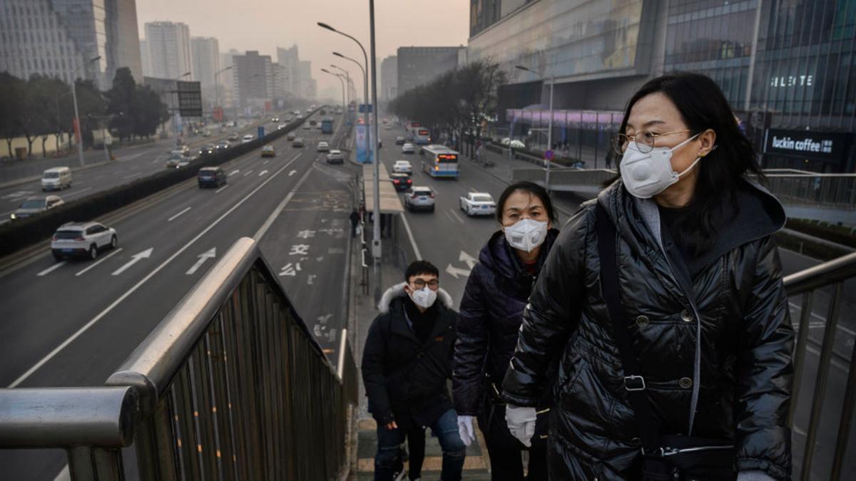 中共當局要求各地儘快復工,人們擔憂恐導致疫情擴散。圖為北京街上戴口罩的市民。(Kevin Frayer/Getty Images)