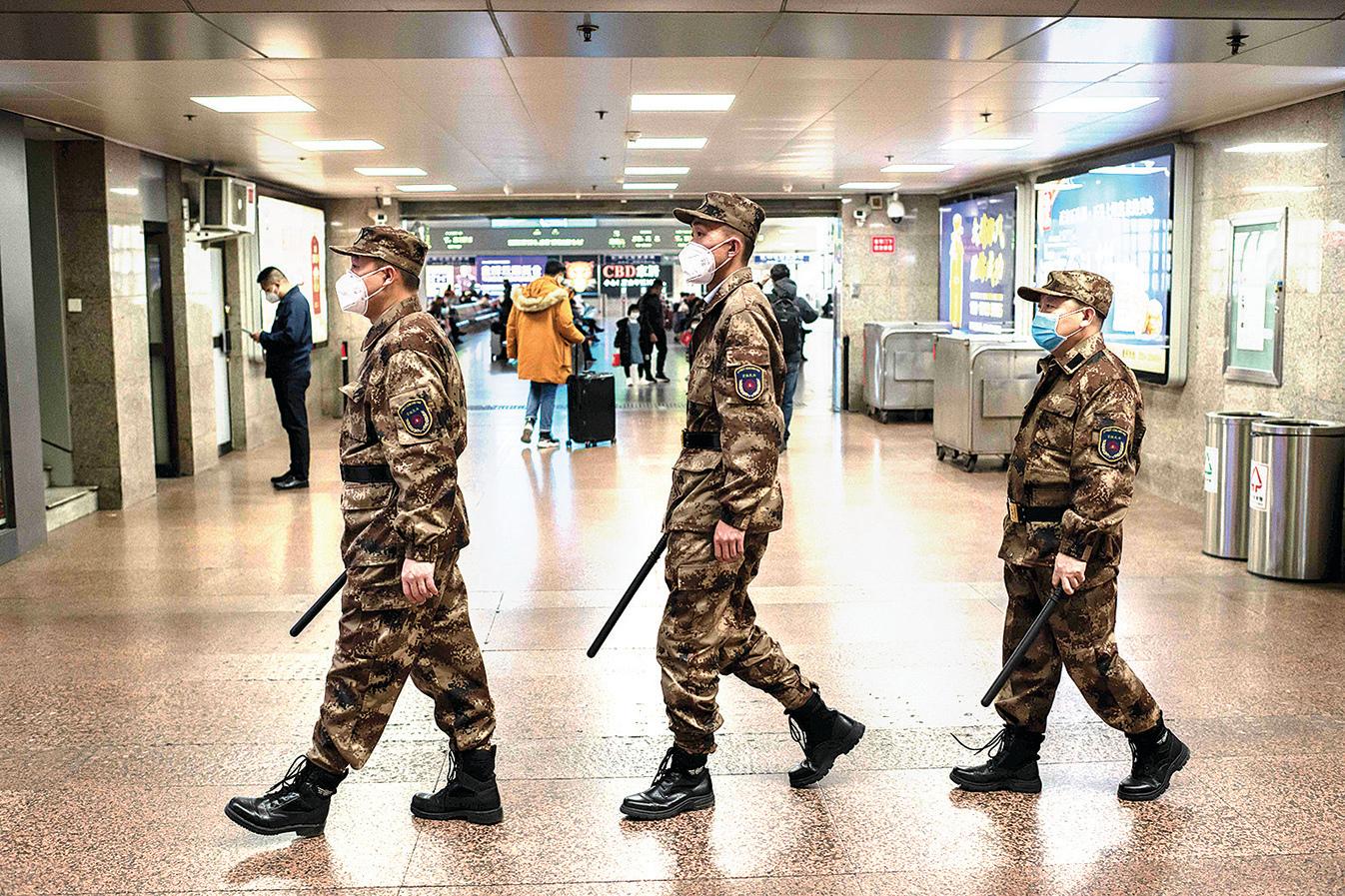 1月24日,在北京西站巡邏的3名穿迷彩服的「京鐵民兵」。(AFP)