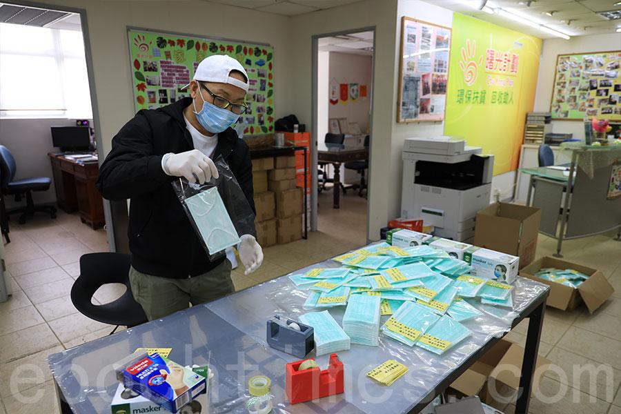 「曙光計劃」主席何峻維連夜包裝了約500份口罩,於2月11日在屯門友愛邨及深水埗麗安邨派發給長者。(陳仲明/大紀元)